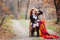 La muchacha pelirroja en hojas de otoño Fotografía de archivo