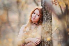 La muchacha pelirroja en hojas de otoño Imagen de archivo
