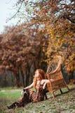 La muchacha pelirroja en hojas de otoño Foto de archivo libre de regalías