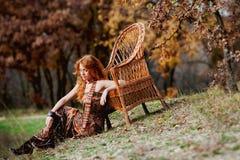 La muchacha pelirroja en hojas de otoño Imagen de archivo libre de regalías