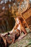 La muchacha pelirroja en hojas de otoño Imágenes de archivo libres de regalías