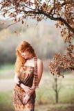 La muchacha pelirroja en hojas de otoño Imagenes de archivo