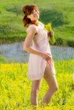 La muchacha pelirroja en prado con flores amarillas y una sonrisa Imagen de archivo
