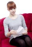 La muchacha pelirroja hermosa joven se sienta en el sofá rojo y recibió un l Fotos de archivo