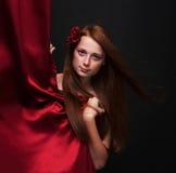 La muchacha pelirroja hermosa mira hacia fuera de detrás un Cu rojo del teatro Imagen de archivo libre de regalías