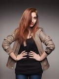 La muchacha pelirroja joven en una chaqueta de cuero representa el modelo Imagenes de archivo