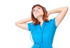 La muchacha pelirroja joven escucha la música y baila Fotografía de archivo libre de regalías