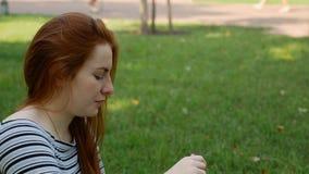 La muchacha pelirroja sopla burbujas de jabón en el parque almacen de metraje de vídeo