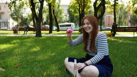 La muchacha pelirroja sopla burbujas de jabón en el parque almacen de video