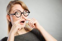 La muchacha pellizca su nariz debido a hedor del hedor imagenes de archivo