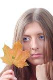 La muchacha pensativa con la hoja del otoño del arce Imagenes de archivo