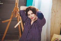 La muchacha pensativa creativa del pintor pinta una imagen colorida en canva Imagen de archivo