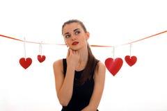 La muchacha pensativa hermosa se coloca cerca de la cinta con los corazones y mira en la distancia Imágenes de archivo libres de regalías