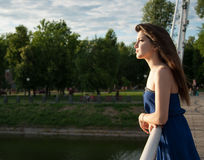 La muchacha pensativa mira en la distancia cerca del río Foto de archivo