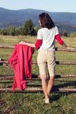 La muchacha pensativa que se inclina en una cerca de madera, da vuelta alrededor y Fotos de archivo
