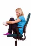 La muchacha pensativa que se relaja en silla sostiene una taza de té o de café. Imagen de archivo libre de regalías