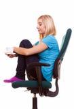 La muchacha pensativa que se relaja en silla sostiene una taza de t Imagen de archivo libre de regalías