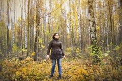 La muchacha permanece en bosque del otoño entre árboles de abedul y hojas del amarillo Foto de archivo
