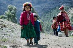 La muchacha peruana nativa y su pequeño hermano se vistieron en equipo hecho a mano tradicional colorido Fotos de archivo libres de regalías