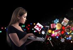La muchacha pide los regalos de la Navidad en una tienda en línea imágenes de archivo libres de regalías