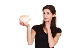 La muchacha piensa en el dinero del ahorro con el moneybox Foto de archivo libre de regalías