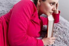 La muchacha piensa en el libro leído Analice la lectura Lea un libro La mujer acabada leyendo el libro Fotografía de archivo