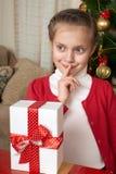 La muchacha piensa en un regalo cerca del árbol de navidad, del día de fiesta feliz y de la celebración del invierno Fotos de archivo libres de regalías