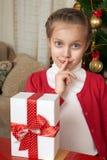 La muchacha piensa en un regalo cerca del árbol de navidad, del día de fiesta feliz y de la celebración del invierno Imagen de archivo