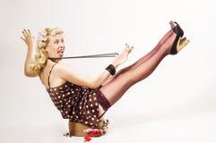 La muchacha Pin-para arriba se sienta en la maleta Imagen de archivo libre de regalías