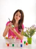 La muchacha pintó los huevos de Pascua en un fondo blanco Foto de archivo
