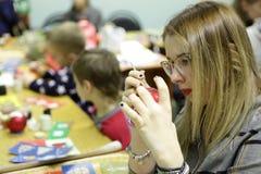 La muchacha pinta el juguete de la Navidad Foto de archivo