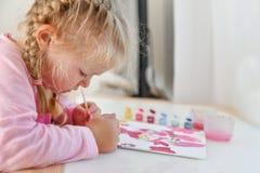 La muchacha pinta la imagen con su mano izquierda en pinturas del color fotos de archivo libres de regalías