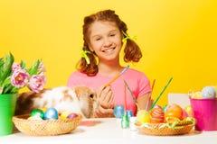 La muchacha pinta los huevos de Pascua con el conejo en la tabla Fotografía de archivo