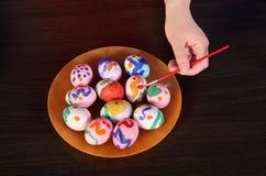 La muchacha pinta los huevos de Pascua mano, cepillo y pintura en la tabla Preparación para Pascua imágenes de archivo libres de regalías
