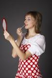 La muchacha pinta los labios Foto de archivo