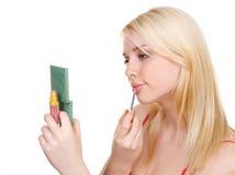 La muchacha pinta los labios Imagen de archivo