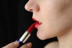 La muchacha pinta los labios con el lápiz labial Foto de archivo libre de regalías
