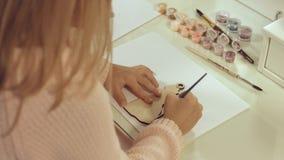 La muchacha pinta un juguete de madera de la Navidad Fotos de archivo