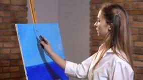 La muchacha pinta una imagen Con la ayuda de una pala crea el cielo 4K MES lento almacen de video