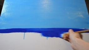 La muchacha pinta una imagen En el marco de la lona, en un movimiento que el artista hace un horizonte azul, después que comienza almacen de video