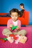 La muchacha plaing con los bloques del juguete (la madre detrás de ella) Imagen de archivo libre de regalías
