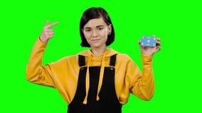 La muchacha plantea una tarjeta y temas en ella Pantalla verde metrajes