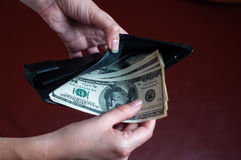 La muchacha pone dólares en monedero Imágenes de archivo libres de regalías