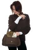La muchacha pone el dinero en un bolso Imagenes de archivo