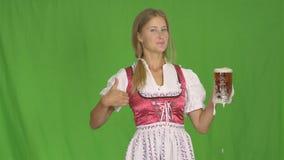 La muchacha pone el vidrio de cerveza en un fondo aislado almacen de video