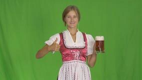 La muchacha pone el vidrio de cerveza en un fondo verde aislado Celebración de Oktoberfest del Bavarian metrajes