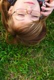 La muchacha pone en una hierba con el teléfono Imagen de archivo libre de regalías