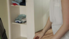 La muchacha pone la ropa interior en una maleta almacen de video