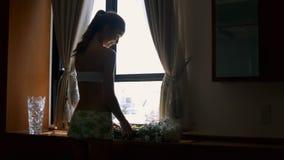 La muchacha pone las flores blancas en raíces de los cortes del travesaño en casa