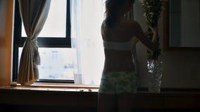 La muchacha pone las flores en el espejo cercano del florero en hotel
